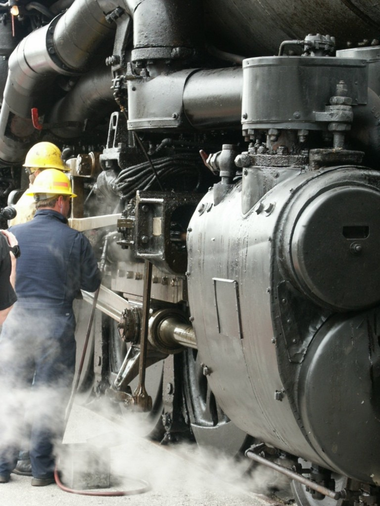 industrial men in hardhats working on a freight train engine