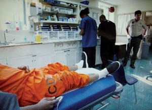 inmate in orange jumpsuit being examined by prison staff