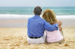 man and woman hugging on beach with backside